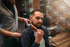 Męski klient czesze jego brodę przy zakładem fryzjerskim Zdjęcia Royalty Free