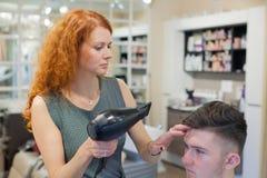 Męski klient dostaje ostrzyżenie Dziewczyna fryzjer suszy mój włosy młody, atrakcyjny facet w piękno salonie, Zdjęcie Stock