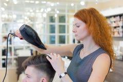 Męski klient dostaje ostrzyżenie Dziewczyna fryzjer suszy mój włosy młody, atrakcyjny facet w piękno salonie, Obraz Stock