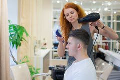 Męski klient dostaje ostrzyżenie Dziewczyna fryzjer suszy mój włosy młody, atrakcyjny facet w piękno salonie, obrazy royalty free