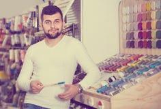 Męski klient egzamininuje różnorodnych typ muśnięcia w farba sklepie Zdjęcia Stock