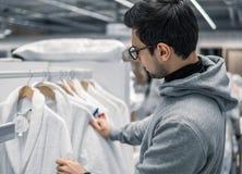 Męski klient sprawdza bathrobe w supermarkecie i kupuje zdjęcie stock