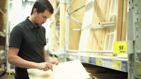 Męski klient stoi blisko półki drewniani rzemiosła w narzędzia sklepie zdjęcie wideo