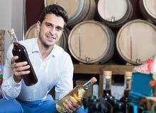 Męski klient trzyma szkło i butelkę wino w sklepie Zdjęcie Stock