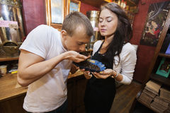 Męski klient wącha kawowe fasole podczas gdy sprzedawcy mienia puchar w sklepie Zdjęcie Stock