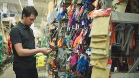 Męski klient wybiera ogrodowe rękawiczki w narzędzia sklepie zbiory