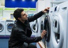 Męski klient wybiera pralkę w supermarkecie fotografia stock