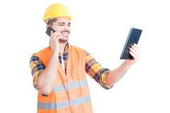 Męski konstruktor z nowożytną pastylką używać telefon komórkowego i ono uśmiecha się Obraz Stock