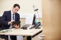 Męski konsultant Używa Cyfrowej pastylkę Przy biurkiem W biurze obrazy royalty free