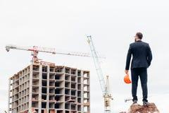 Męski kontrahent lub cywilny inżynier patrzeje budynku projekt na postępie fotografia royalty free