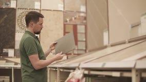 Męski kupujący jest przyglądający na ceramiczne płytki w budynku sklepie zbiory wideo