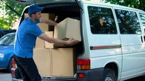 Męski kurier bierze dostawę boksuje za samochodzie dostawczym od, poruszająca firma, towarowy transport obraz royalty free