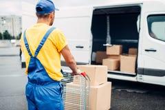 Męski kurier w jednolitej pracie z ładunkiem, tylny widok Zdjęcia Royalty Free