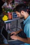 Męski kwiaciarni obsiadanie i używać laptop Obrazy Royalty Free