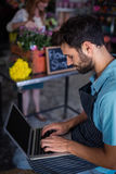 Męski kwiaciarni obsiadanie i używać laptop Zdjęcie Stock