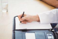 Męski lekarki ręki writing na kartotece Zdjęcia Stock
