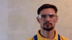 Męski malarz jest ubranym zbawczych szkła i pokazuje aprobaty w błękitnych coveralls zbiory wideo