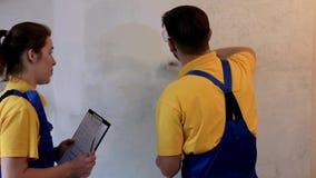 Męski malarz maluje ścianę z białym kolorem w błękitnych coveralls zdjęcie wideo