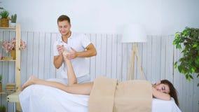 Męski masażysta masuje piękną młodej kobiety nogi stopę na stole w zdroju salonie zdjęcie wideo