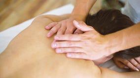 Męski masażysta masuje piękną młodej kobiety szyję na stole w zdroju centrum zbliżeniu zbiory wideo