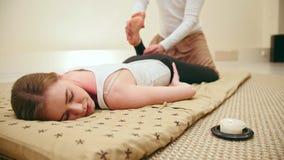 Męski masażysta trzyma tajlandzkiej masaż sesi - nogi rozciąga dla ślicznego blondynka modela zdjęcie wideo