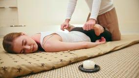 Męski masażysta trzyma tajlandzkiej masaż sesi - rozciąganie nogi, suwak zbiory wideo