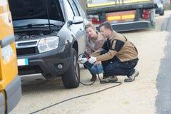 Męski mechanik nadyma samochodową oponę blisko żeńskiego klienta Obrazy Royalty Free
