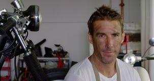 Męski mechanik pije kawę w motocykl naprawy garażu 4k zbiory wideo