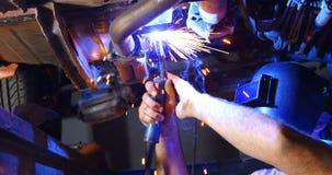 Męski mechanik używa płomienną pochodnię 4k zbiory