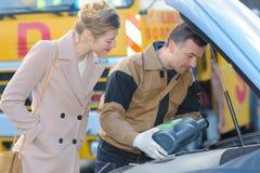 Męski mechanik wypełnia nafcianego zbiornika kobiety ładnego klienta Zdjęcie Stock