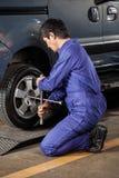Męski mechanik Załatwia Samochodową oponę Przy Remontowym sklepem Fotografia Royalty Free
