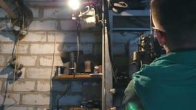 Męski mechanik załatwia samochodowego szczegół Mężczyzna w workwear pracuje w garażu lub warsztacie Ciężkiej Pracy Pojęcie Tylny  zbiory wideo