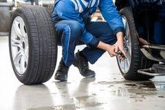 Męski mechanik Zmienia Samochodową oponę W garażu Zdjęcia Royalty Free