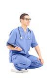 Męski medycznego pracownika przycupnięcie i mienie schowek Obraz Stock