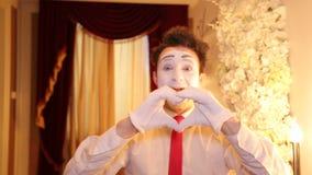 Męski mima artysta z białą twarzą pokazuje parodie zbiory