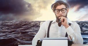 Męski modniś trzyma tabaczną drymbę podczas gdy patrzejący maszyna do pisania przeciw morzu Zdjęcie Royalty Free