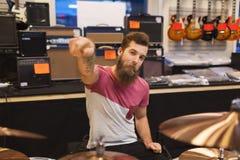 Męski muzyk bawić się cymbałki przy muzycznym sklepem Obrazy Royalty Free