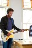 Męski muzyk bawić się gitarę elektryczną w domowym studiu Fotografia Royalty Free