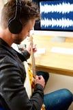 Męski muzyk bawić się gitarę elektryczną z słuchawkami Fotografia Stock