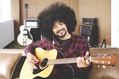Męski muzyk bawić się gitarę w studiu nagrań zdjęcie royalty free