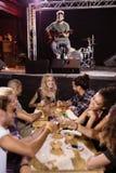 Męski muzyka śpiew z fan siedzi przy stołem Zdjęcia Royalty Free