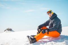 Męski narciarki obsiadanie na śnieżny relaksować Zdjęcia Royalty Free