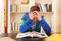 Męski nastolatek martwiący się robić pracie domowej fotografia stock