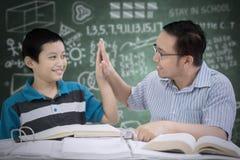 Męski nauczyciel daje wysokości pięć jego uczeń Obraz Stock