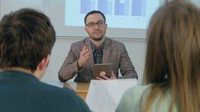 Męski nauczyciel trzyma pastylki obsiadanie przed klasą zbiory