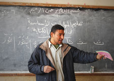 Męski nauczyciel wyjaśnia na blackboard w sala lekcyjnej Fotografia Stock