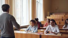 Męski nauczyciel wyjaśnia nową informację etniczna grupa ucznie które piszą w notatnikach bierze notatki zdjęcie wideo