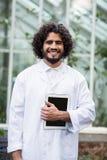 Męski naukowiec trzyma cyfrową pastylkę na zewnątrz szklarni Obraz Stock