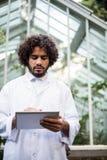 Męski naukowiec używa pastylka komputer na zewnątrz szklarni Zdjęcia Royalty Free