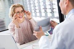 Męski okulista oferuje szkło ramy starsza kobieta Obraz Royalty Free